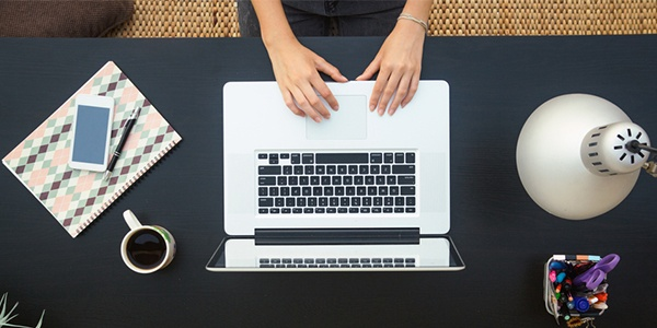 Typing on a laptop at a desk